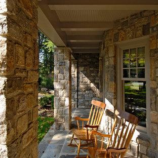Immagine di un portico vittoriano davanti casa con pavimentazioni in pietra naturale e un tetto a sbalzo