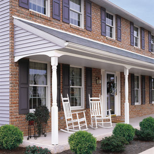 Mid-sized trendy concrete front porch photo in Other with a roof extension