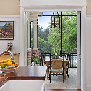 Immagine di un portico chic di medie dimensioni e dietro casa con un portico chiuso e pavimentazioni in mattoni