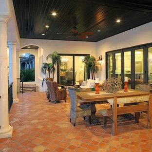 Свежая идея для дизайна: огромная веранда на заднем дворе в средиземноморском стиле с покрытием из плитки и навесом - отличное фото интерьера