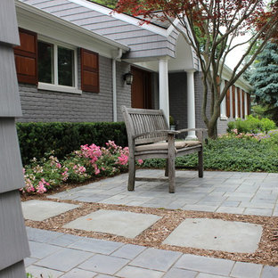 This is an example of a small transitional stone front porch design in Detroit.