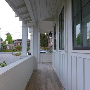 Esempio di un ampio portico country davanti casa con pavimentazioni in mattoni e un tetto a sbalzo