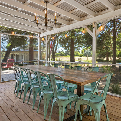 This is an example of a cottage screened-in back porch design in San Francisco with decking and a roof extension.