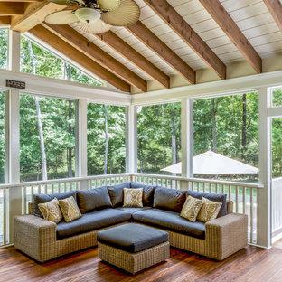 Ejemplo de porche cerrado clásico, grande, en patio trasero y anexo de casas, con entablado