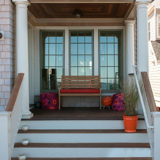 Mid-sized beach style front porch idea in New York with decking and a roof extension