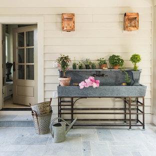 Foto di un patio o portico country di medie dimensioni e dietro casa con un giardino in vaso, pavimentazioni in pietra naturale e un tetto a sbalzo