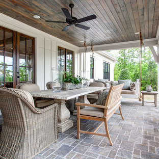 Bild på en stor vintage veranda på baksidan av huset, med naturstensplattor och takförlängning
