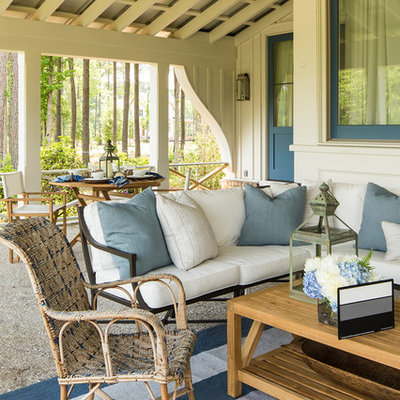 This is an example of a coastal porch design in Charlotte with a roof extension.