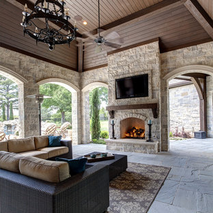 Tuscan porch idea in Dallas with a fire pit and a roof extension