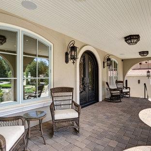 Неиссякаемый источник вдохновения для домашнего уюта: огромная веранда на переднем дворе в средиземноморском стиле с мощением тротуарной плиткой и навесом