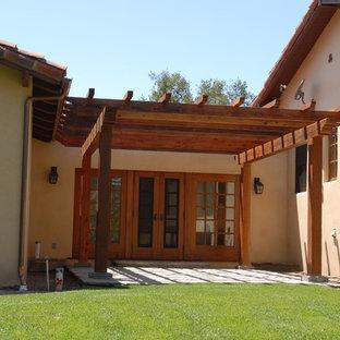 Large tuscan side porch idea in San Luis Obispo with a pergola