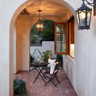 Свежая идея для дизайна: веранда в средиземноморском стиле с мощением клинкерной брусчаткой и навесом - отличное фото интерьера