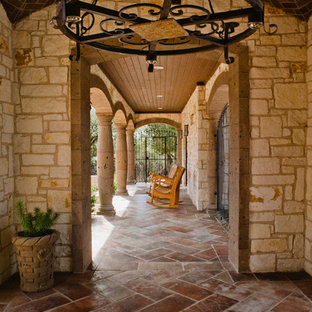 This is an example of a huge southwestern tile front porch design in Austin with a roof extension.