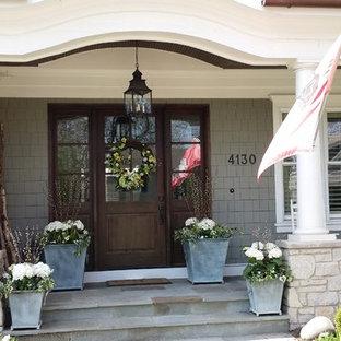 Idee per un piccolo portico american style davanti casa con un giardino in vaso, pavimentazioni in cemento e un tetto a sbalzo