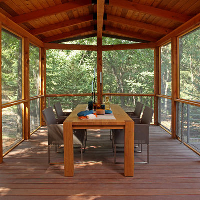 Large mountain style screened-in side porch idea in Minneapolis with decking and a roof extension