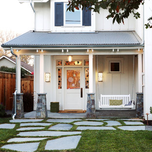 Mid-sized farmhouse stone front porch photo in Denver with a roof extension