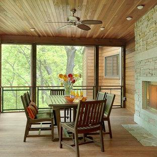 Foto på en lantlig veranda, med en öppen spis och takförlängning