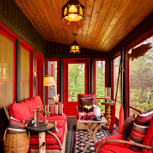 This is an example of a rustic screened-in porch design in Milwaukee with decking.