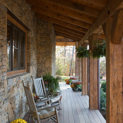 This is an example of a large rustic front porch design in Other with decking and a roof extension.