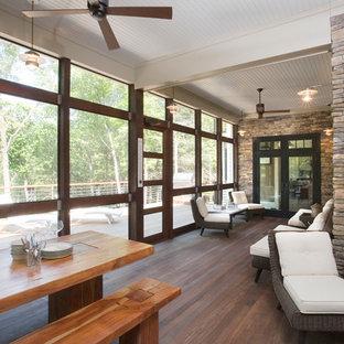 Esempio di un grande portico stile americano dietro casa con un portico chiuso, pedane e un tetto a sbalzo