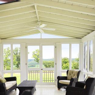 Esempio di un patio o portico country con pedane, un tetto a sbalzo e un portico chiuso
