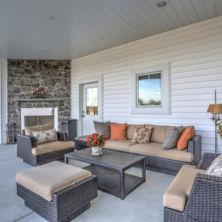 Country concrete back porch idea in Other with a fire pit and a roof extension
