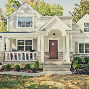 This is an example of a mid-sized traditional concrete front porch design in Cincinnati with a roof extension.