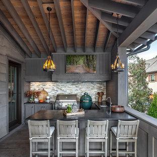 Aménagement d'un grand porche avec une cuisine extérieure arrière campagne avec une terrasse en bois et une extension de toiture.