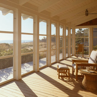 This is an example of a traditional screened-in porch design in Philadelphia with decking and a roof extension.