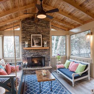 Immagine di un portico shabby-chic style di medie dimensioni e dietro casa con un portico chiuso, piastrelle e un tetto a sbalzo