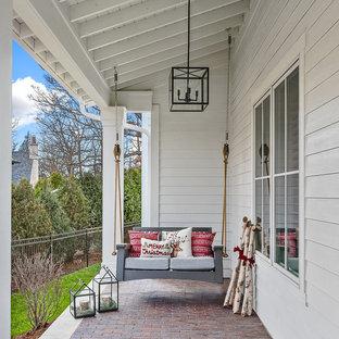 Immagine di un portico country con pavimentazioni in mattoni e un tetto a sbalzo