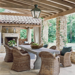 Inspiration for a large mediterranean stone back porch remodel in Houston with a fire pit and a pergola