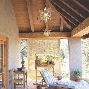 This is an example of a mid-sized southwestern front porch design in Albuquerque with decking and a roof extension.