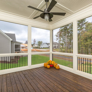 This is an example of a mid-sized cottage screened-in back porch design in Raleigh with decking and a roof extension.