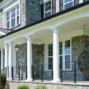 Idee per un ampio portico tradizionale davanti casa con pavimentazioni in pietra naturale, un tetto a sbalzo e parapetto in metallo