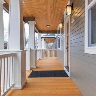 Foto di un portico stile americano davanti casa con pedane e un tetto a sbalzo