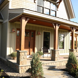 Large farmhouse stone porch idea in Boston with an awning