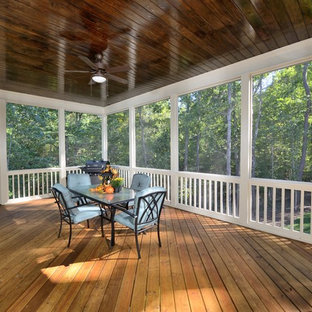 This is an example of a traditional screened-in back porch design in Raleigh with decking and a roof extension.