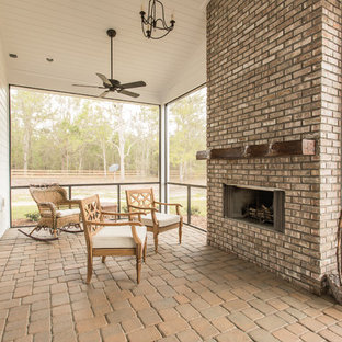 Inspiration for a mid-sized country brick screened-in back porch remodel in Orlando with a roof extension