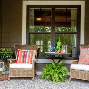 Immagine di un piccolo portico american style davanti casa con un giardino in vaso, lastre di cemento e un tetto a sbalzo