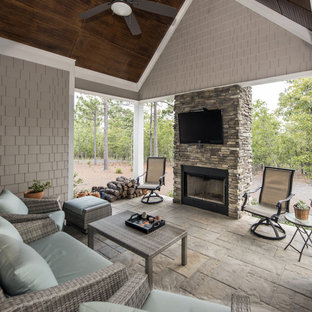Classic stone back porch idea in Other with a fire pit and a roof extension