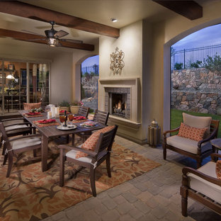 This is an example of a mediterranean back porch design in Denver with a fire pit.