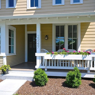 This is an example of a large craftsman front porch design in Indianapolis with a roof extension.