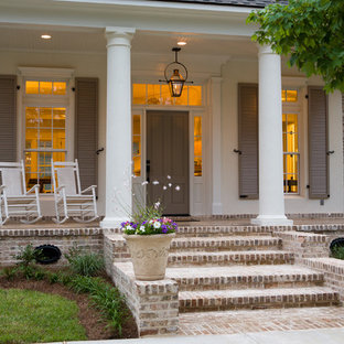 Inspiration for a large timeless brick front porch remodel in New Orleans with a roof extension