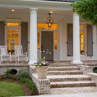 На фото: большая веранда на переднем дворе в классическом стиле с мощением клинкерной брусчаткой и навесом с