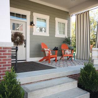 Idee per un portico stile americano davanti casa con lastre di cemento e un tetto a sbalzo