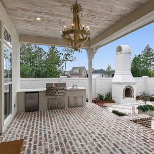 Idee per un grande portico chic dietro casa con pavimentazioni in mattoni e un tetto a sbalzo
