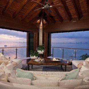 Immagine di un portico tropicale di medie dimensioni e dietro casa con un tetto a sbalzo, un portico chiuso e pedane