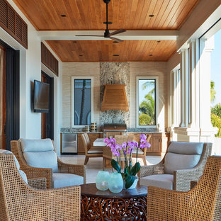 This is an example of a mid-sized tropical tile porch design in Miami with a roof extension.