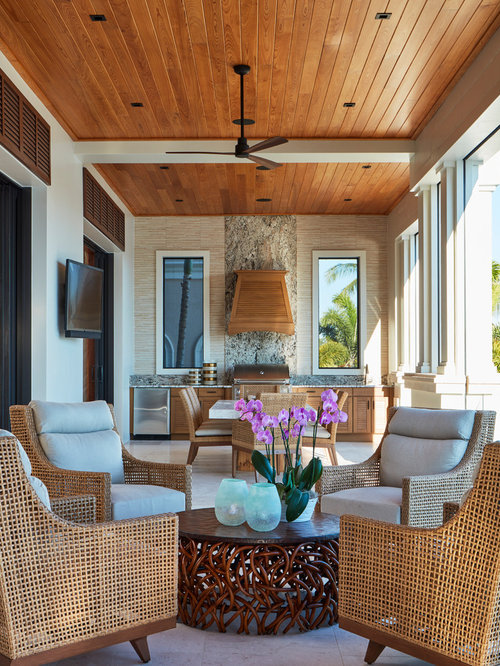 This is an example of a mid-sized tropical tile porch design in Miami with